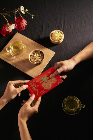 "Chinese Lunar New Year concept red envelope with Chinese character means happiness or good fortune, the chinese sentence means ""Wishing you prosperity"" and ""May all your wishes come true""."