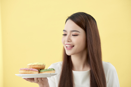 Asian girl show and holding plate full of tasty delicious aromatic donuts in smile face isolated.