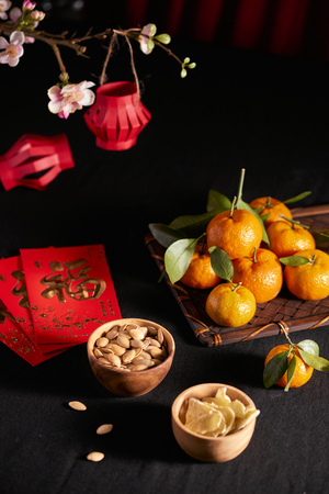 Concept image of the lunar new year - mandarin orange, jam and red packet. Text on envelop means Happy New Year and Happiness. 免版税图像