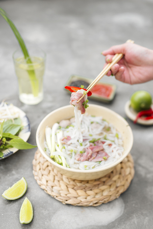 Vietnamese Pho Noodle Soup. Beef with Chilli, Basil, Rice Noodles, Bean Shoots showing noodles picked up with Chopsticks Stock Photo
