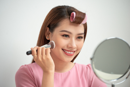 Gorgeous young brunette woman applying makeup