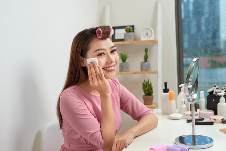 Cosmetic beauty procedures and makeover concept. Woman in hair curlers beautiful young woman using cotton pads at home Standard-Bild - 115694834