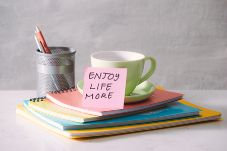 Green cup, notebooks and sticker with text - enjoy life more on light background. Toned business concept with copy space Stock Photo