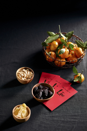 Amazing of Vietnamese food for Tet holiday in spring, tangerine and jam is traditional food on lunar new year, make from jujube jam, pumpkin seed, ginger with sugar. Text on envelop means Happy New Ye