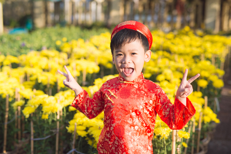 Having fun asian kid at marigold garden. Portrait of funny kid wearing Vietnamese traditional dress (Ao Dai) at Tet holiday 스톡 콘텐츠