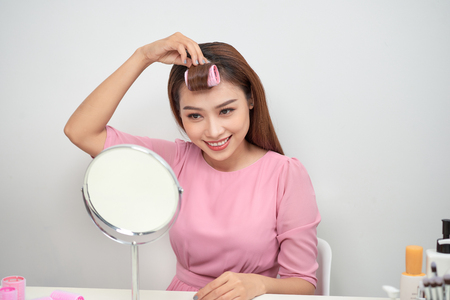 Beautiful woman with curlers smiling into mirror, enjoying her look, beauty Banque d'images - 115329301