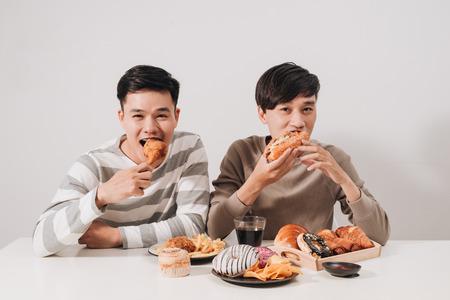 Dos amigos comiendo hamburguesas. papas fritas, divertirse y sonreír