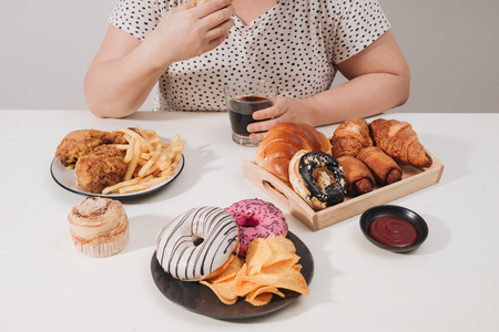 Kurvige Frau, die sich darauf vorbereitet, Hamburger zu essen, übermäßiges Essproblem, Depressionen Standard-Bild