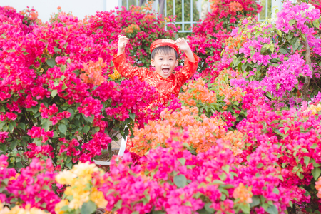 Portrait of a handsome Asian boy on traditional festival costume standing near Hoa Giay tree (Bougainvillea) flower. Cute little Vietnamese boy in ao dai dress smiling