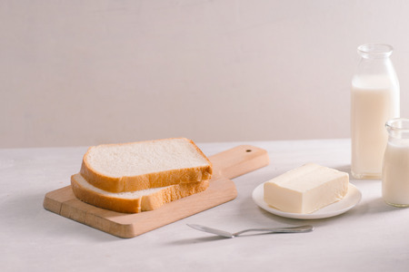 Sliced bread bake and butter on wooden cutting board. Simple breakfast