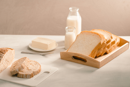 Bread on plate holder surrounded by butter and milk on white table close-up