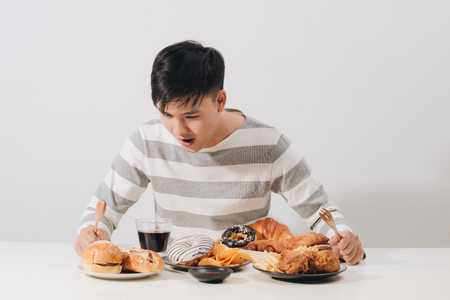 Young man at home on a unhealthy diet