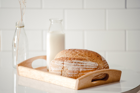 Glass bottle of milk with bread on wooden tray isolated on white background for food and healthy concept. with copy space for text