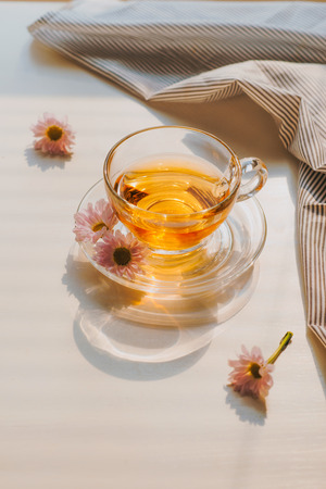 Cup of herbal chamomile tea on a table. Chamomile tea in a transparent cup and camomile flowers on table. Banco de Imagens