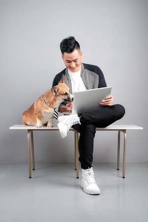 Handsome young businessman is using laptop while sitting with his dog on chair Banque d'images - 115694975