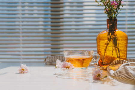 Cup of herbal chamomile tea on a table. Chamomile tea in a transparent cup and camomile flowers on table. Zdjęcie Seryjne