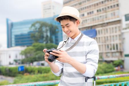 Atractivo joven, estudiante o fotógrafo independiente sonríe y se ríe a la cámara Foto de archivo