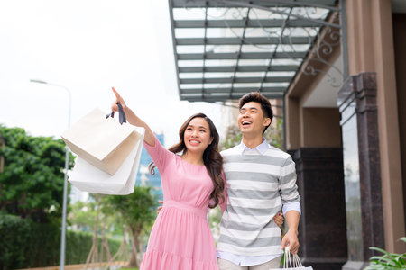 Portrait of happy couple with shopping bags after shopping in city smiling and huging. Standard-Bild