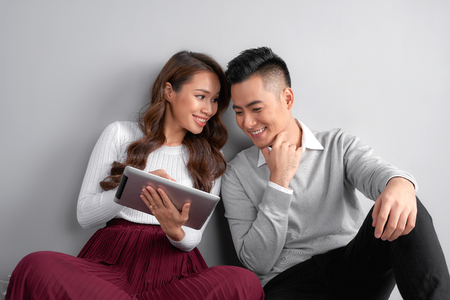 Happy young couple using tablet sitting on the floor at home isolated on gray background