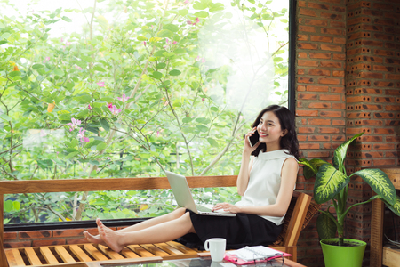Confident young asian woman in smart casual wear talk on phone.