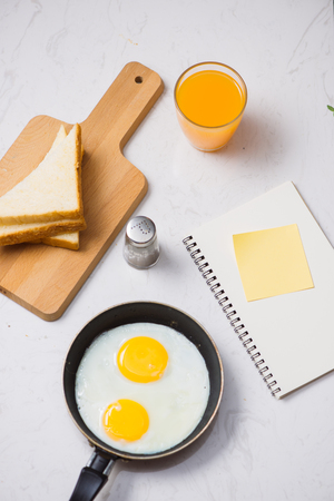 Eating in the process, fried eggs in a frying pan, toast  and orange juice for breakfast on a white background. Daylight.