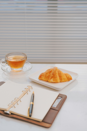 business work on marble table coffee with croissant bakery