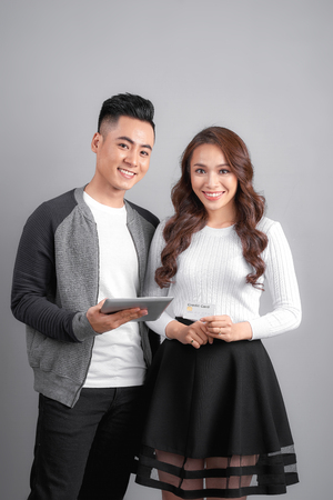 technology, people, e-money and commerce concept - smiling happy couple with tablet pc computer and credit or bank card shopping online