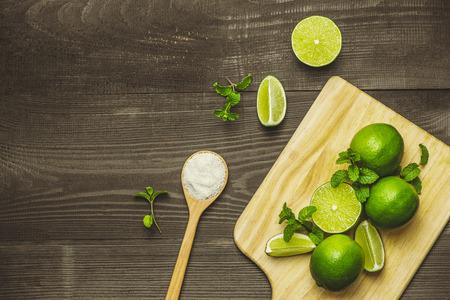 Fresh sliced lime and salt on wood table.