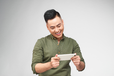 Excited bearded man in plaid shirt playing on smartphone over white background 스톡 콘텐츠