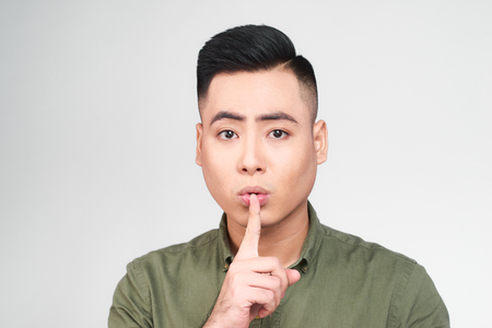 Pleasant looking delightful young male keeps finger on lips, asks not tell secret information or keep silence, isolated over gray background. Attractive bearded man gestures at home 版權商用圖片