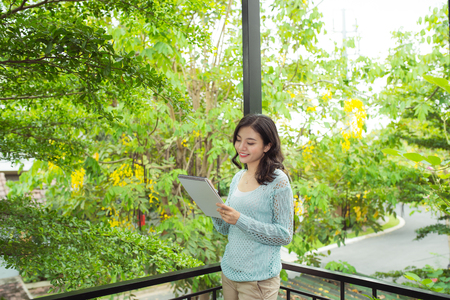 Young attractive sweet girl with notepad on a veranda. Spring mood. Stock fotó