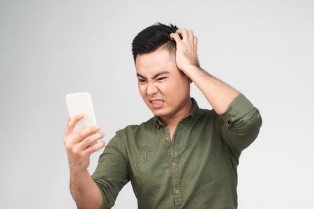 Porträt eines müden männlichen Studenten, der auf weißen Artikeln isoliert ist und mit seinem Smartphone nach Informationen im Internet sucht. Unruhiger Mann, der mit emotionalem Gesichtsausdruck recherchiert