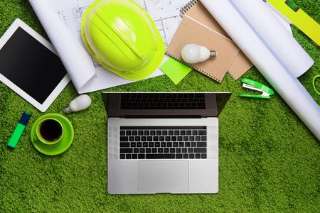 Lieu de travail avec casque, plans, ordinateur portable et bloc-notes sur fond d'herbe. Vue de dessus avec espace de copie