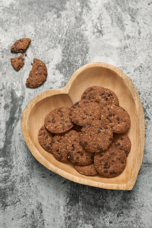 Chocolate chip cookies on heart-shape plate on grey stone background