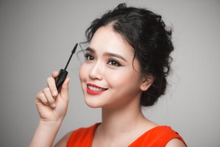 An asian woman applying mascara on her eyelashes