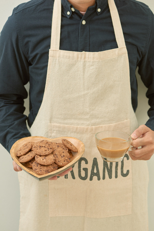 Plate of cookies in male hands on dark old wooden background top view 스톡 콘텐츠