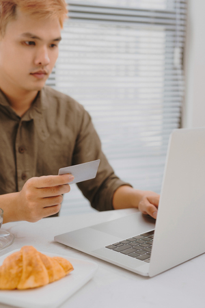 Modern technology, business, career, e-commerce and online trading concept. Asian businessman holding credit card in one had and keyboarding on laptop with other hand, making transaction