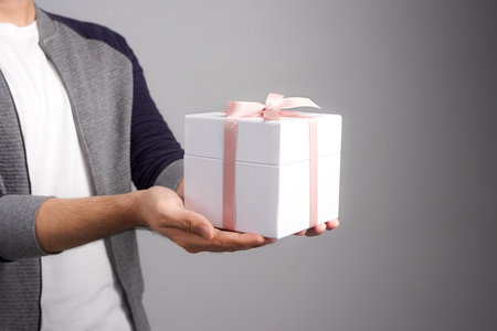 Male hands holding a gift box. Present wrapped with ribbon and bow. Christmas or birthday package