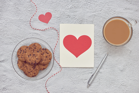 Chocolate chip cookies on plate and glass of milk coffee with love message card on white stone background