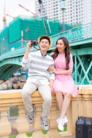 Young man and pretty girl are having fun in the city at evening.