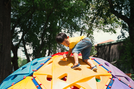 Asian kid boy having fun to play on childrens climbing toy at school playground, back to school outdoor activity.