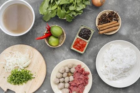 Traditional vietnamese noodle soups pho in bowls, concrete background. Vietnamese beef soup pho bo, Close-up. Asian/vietnamese food. Vietnamese dinner. Pho bo meal. Top view. Healthy Stok Fotoğraf - 115721813