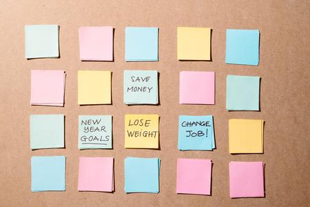 objectifs ou résolutions du nouvel an - notes autocollantes colorées sur un bloc-notes avec une tasse de café.