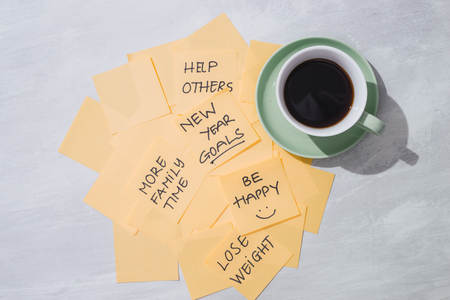 new year goals or resolutions - yellow sticky notes with coffee on table