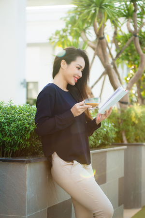 Happy young woman holding book fond of literature analyzing novel during leisure time on terrace of campus cafe in sunny day.