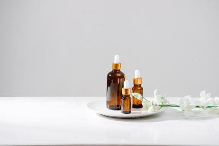 Spa-Einstellung mit Orchideen und ätherischem Öl in einer Glasflasche, Aromatherapie-Konzept Standard-Bild