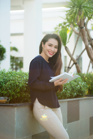 Portrait of smiling female student reading book while standing outdoor on terrace of campus cafe in sunny day. Education, lifestyle and people concept. Stock Photo
