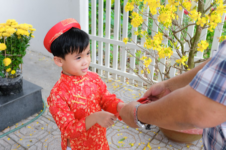 Grandfather giving lucky money to grandson on the first day of Vietnamese lunar new year Tet Standard-Bild - 116099098