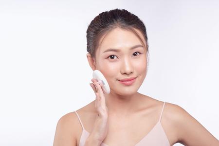 Smiling girl holding powder cushion puff applying cosmetic powder on face