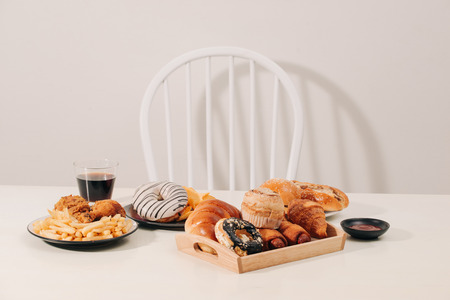 fast food and unhealthy eating concept - close up of hamburger or cheeseburger, deep-fried squid rings, french fries, drink and ketchup on wooden table Stockfoto